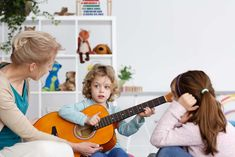 Senior blonde teacher showing little boy how to play a guitar, photo with copy space , Aesthetic Wallpapers, Little Boys, Guitar, Teacher, Play, Space, Design, Baby Swimming, Child Development