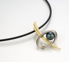 Jhain Pendant by Britt Anderson. 18K white and yellow gold pendant highlighted with an 8mm Tahitian black pearl and a 0.10ct FG-SI1 quality diamond set in a platinum bezel.