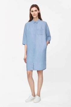 This relaxed shirt dress is made from lightweight fabric that has been woven to look like denim chambray. Designed to fall loosely on the body, it is an oversized shape with hidden buttons, side seam pockets and a single box pleat on the back.