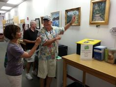 Grace, John and Roy discuss the best way to hang the paintings for the new Sebastian Art Club exhibit.