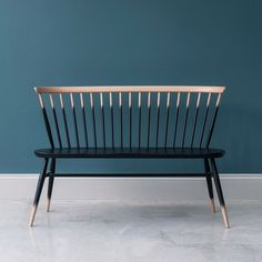 ercol Originals Loveseat by Lucian Ercolani A classic Windsor style bench with a solid timber seat molded for comfort. Opt for a natural wood finish, or add a touch of modern edge with a graded paint