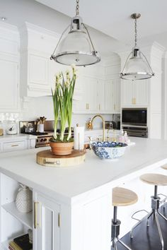 Classic white kitchen with industrial pendant and stools