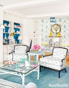 White walls, blue printed wall paper, white shelves, mirrored cabinets, printed white and blue chairs, blue rug, clear coffee table, and light blue side table