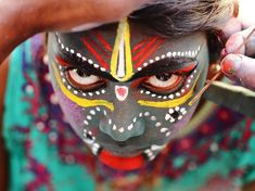 Picture of a young girl having her face painted for the Angalamman festival, Tamil Nadu, India