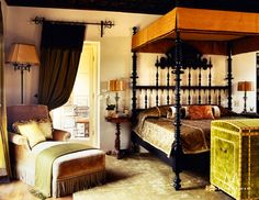 The master bedroom of a c.1923 residence in Pasadena is highlighted by a custom Portuguese-inspired bed, a silk velvet TV trunk and a linen velvet chaise. Note the portieres softening the opening to the bathroom. Madeline Stuart