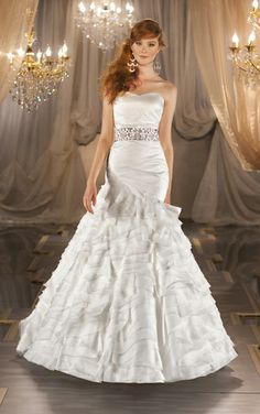 Martina Liana 396  Silk Organza fit-and-flare designer wedding gown features an asymmetrical dropped waist, and sculptural ruffles on its tiered silk skirt. Lace up or zipper back. Satin beaded sash sold separately.