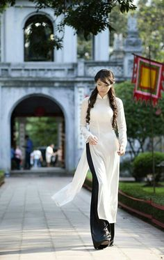 The ao dai is the traditional dress in Vietnam. In modern times, it's basically a long tight-fitting silk tunic (with high slits as far as I can see worn with palazzo-type pants. It also seems to have a pretty high neck as a design thing, maybe because of their tradition? It looks kind of like a super long kurta with high slits.