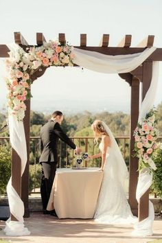 construction en bois décorée de rideaux et de fleurs, décoration arche mariage en plein air