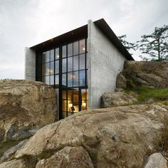 Concrete house by Olson Kundig Architects cuts into a rocky outcrop on a USA island.