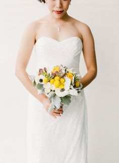 A yellow and white bouquet of anemones, billy balls, succulents, roses, and dusty miller {Brian Saculles Photography}