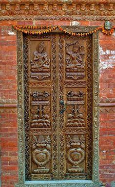 Ornate carved wooden door in Swayambhunath, Nepal |