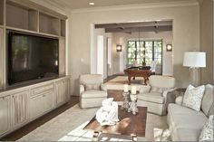 "CDT: ""In this family room,  Tami Owen had a shelving unit built in to hold a HUGE flatscreen.  She cut out doors and added fabric for the electronics and speakers.  Plus, the fabric softens the piece.   With a TV this huge, you need something substantial to ground it."""