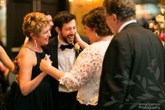 Photojournalistic wedding reception photograph of guests laughing