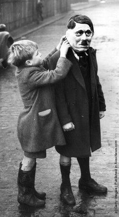 A young boy adjusts his friend's Hitler mask during a game on a street in London, 1938