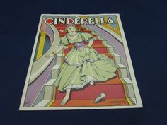 """Vintage Cinderella Linen Book. This little booklet is a Linenette book. It is the story of Cinderella. The book is no. 427 and printed in the United States. There is 10 pages in the booklet. The illustrations are brightly colored. The book is approx. 8 1/4"""" x 7 1/4"""". It is in good condition with some wear and aging. There is some damage to the front cover. There is some creasing to the pages as well."""