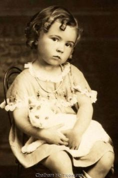 Little girl with ringlets holding a white cat