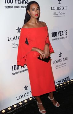 Solange Knowles wearing a red off-the-shoulder dress with nude sandals