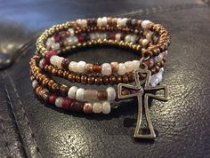 Bronze and brown memory wire bracelet with cross charm.