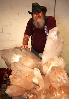 Jim Coleman, owner of Jim Coleman Crystal Mines in Jessieville, stands behind a large quartz crystal cluster, only half of which is showing. Clusters of this size and quality have been known to sell for as much as $1 million or more.