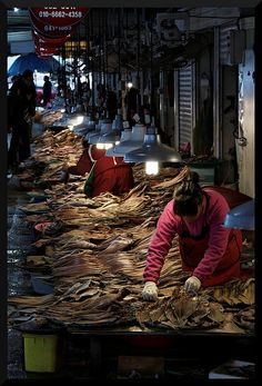 Fish Market in Yeosu, Korea Everything about this is wonderful. Plentiful fish, lines of lamps, metal, grit, and air...just love it!