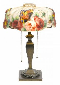 Pairpoint reverse painted puffy glass and patinated metal Butterflies and Roses table lamp first quarter 20th century first quarter 20th centurythe Papillon shade with exterior gilt accents base stamped with a P within a diamond and PAIRPOINT MFG CO. B3038. Height 21in (53.4cm); diameter 14in (35.6cm)