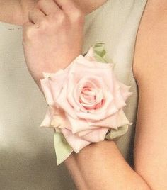 One flower wrist corsage for bridesmaids.  Whatever the flower is, repeat in corsage for mother of groom.
