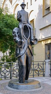 The statue is a man with no head or arms, with another man sitting on his shoulders.