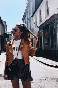 Tan suede jacket over white tee with cute black and white polka dot mini skirt.