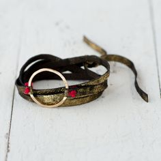 This simple leather wrap gains a touch of shine thanks to a gilded finish and hammered ring detail, each one hand-crafted- so why can't you! DIY perfection- with a touch of red thread stitch to close!