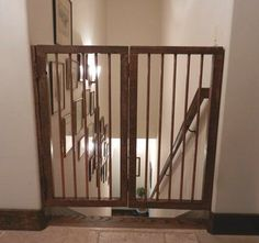 """Custom stair gates from salvaged wood & copper piping."" Cats can still slip under gate but not the dog! Gate is hinged so folds against the wall when open. Could add vintage strap hinges &/or decorative handles/Etsy finds perhaps! #PetGate #catifying #cats #dogs #pets."