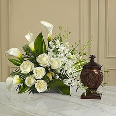 This extraordinary mixed flower bouquet is an excellent choice for creating a beautiful, serene and reverential setting for an urn. The asymmetrical arrangement is hand-arranged and includes Dendrobium orchids, roses, calla lilies, and lush, complementary greenery in a low silvery plastic rectangular container. Beautiful on its own or to enhance a display of a meaningful memento, photograph or candle. Bouquet sizes are approximate.