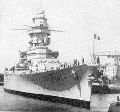 "Bows-on shot of French Battlecruiser ""Strasbourg."" Distinguishable from sister ""Dunkerque"" by extra level on her bridge structure. Under her accomplished commander, Capitaine de vaisseau Louis Edmond Collinet, escaped destruction by the British at Mers el Kebir in July 1940 (the British were afraid the Vichy France government would hand over warships to Germany). Scuttled at Toulon to prevent German capture,  November 1942."