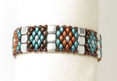 This bracelet is a simple, eye catching design. Silver Czechmate tile beads are woven to separate sections of Superduos that have been beaded together to form a diamond pattern. The colors reflect a southwest flair in earthy tones. The clasp is a Superduo beaded loop that slides over an antique silver button with a decorative design. When the bracelet is clasped it measures 7 around and is 3/4 wide. **************************************************** All jewelry is packaged ready for gift…