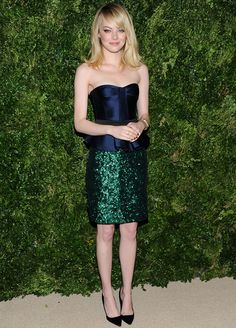 Emma Stone deja las lentejuelas sólo para su falda en verde esmeralda que combina con un top de satén azul marino palabra de honor entallado con cinturón negro para darle un efecto peplum, todo de Burberry Prorsum Spring 2013.