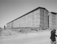 """""""Men walk past the south-east wing of a hostel for Black male workers, erected during apartheid as part of a scheme to make Joburg city and suburbs 'White', Alexandra Township, 1 June David Goldblatt, News South Africa, Vertical Farming, Photo Report, Country Landscaping, Built Environment, Urban Planning, Urban Landscape, Houses"""