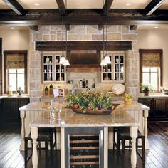Casual Entertaining #Kitchen | In the kitchen, a large T-shaped island provides a prep area for cooking and a casual dining surface surrounded by stools. This separate space allows partygoers to get drinks without crowding the cook.