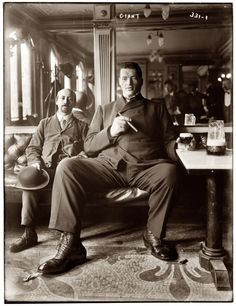 Big man enjoying a cigar and glass of beer in a New York tavern circa 1908.