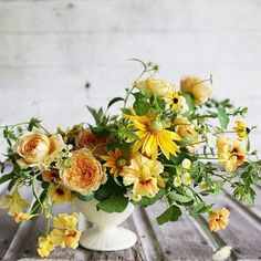 Cheerful yellow and green floral arrangement with garden roses, daisies, and nasturtiums.
