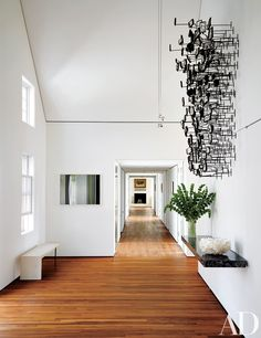 The room's entry is highlighted by a Graham Caldwell sculpture and a Penelope Umbrico photograph; a Meier/Ferrer bench rests on the reclaimed-teak floor.