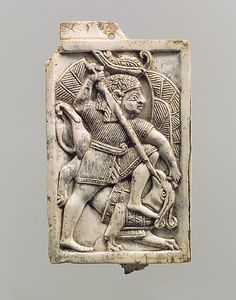 Plaque with a figure in an Egyptian-style red crown, slaying a griffin Period…