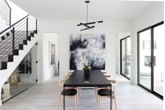 The Daikon Studio 3 Branch Stilk Chandelier hangs over the black dining room table. The artwork is a commissioned piece by Michael Wall.