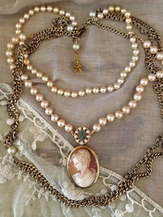 A vintage assemblage four strand draping necklace glass pearls gold tone chains antique shell cameo jade stone medallion