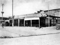 View of the Agustín Olvera adobe c. 1880s, located on the corner of Marchessault and Olvera streets, after it had been converted into office space for Murray & Ready. A man can be seen riding his bicycle on the unpaved road toward the left.
