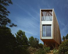 bonte and migozzi's timber cabin nestled amidst luscious green pine groves in greece
