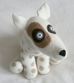 austin the sock dog is white with tan spots with brown and grey patches on both eyes.   he enjoys long walks in the park.