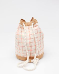 Classic cotton canvas bucket bag with all over screen-printed grid design from Dusen Dusen. Features rounded shape with rope closure and straps.