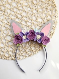 These beautifully sweet bunny ears are made with gray colored felt and accented with different shades of purple and lavendar with a pop of cream and pale blue. Felt bunny ears sit on top of your choice of a 10 mm satin head band, or soft nylon band. Bunny headbands are the perfect