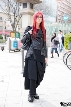 This is Sono, a red-haired girl with glasses. She is 19 years old and she's a student. She is wearing an all black outfit, including a Glimmer top, a biker jacket, Funky Fruit maxi skirt and Yosuke lace-up boots. Her studded bag is Artherapie. Her favorite shop is Glimmer, and she's into the music of Dir en Grey.