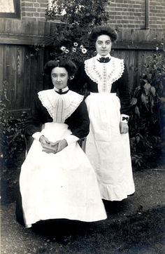This Edwardian photography shows two beautiful dressed up maids in a garden.