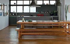 No projeto da SAO Arquitetura, a cozinha virou parte do living depois de aberta para a sala de jantar com mesa e bancos de madeira. Os armários e a ilha central são sóbrios, em cinza chumbo